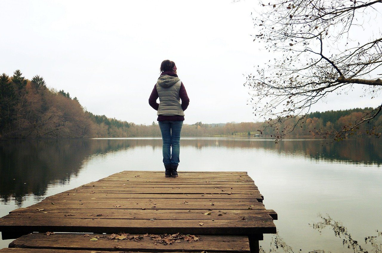 middle-aged woman standing on a jetty overlooking a lake